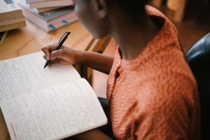 photo-of-woman-writing-on-notebook-3059749